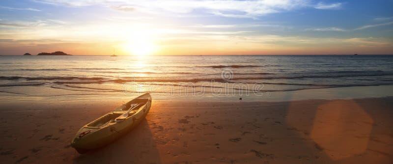 海洋海滩,说谎在岸的独木舟在美妙的日落期间 库存照片