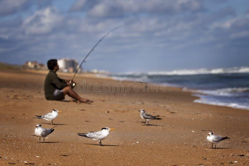 海滩激浪投钓的渔夫 免版税图库摄影