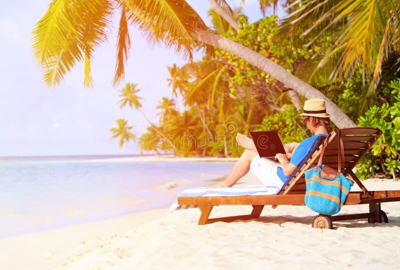 海滩热带膝上型计算机的人 库存图片