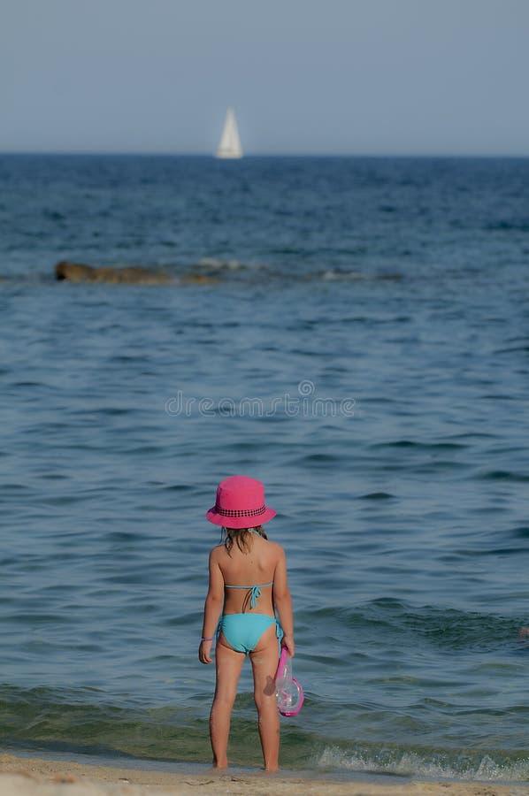 海滩的三个愉快的孩子与五颜六色的面罩 免版税库存照片