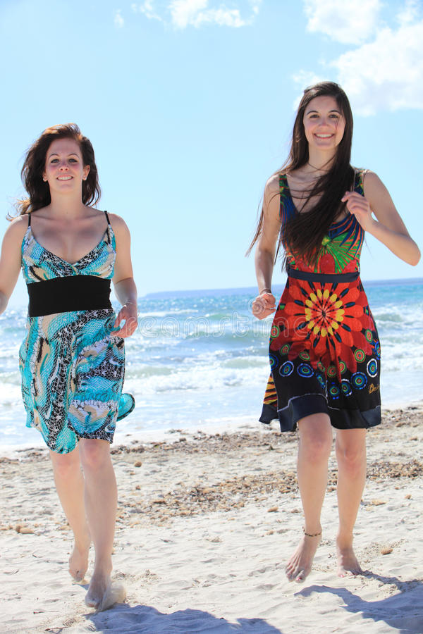 海滩的两名可爱的赤足妇女 免版税图库摄影