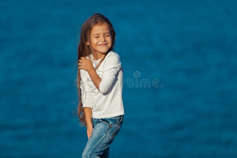 海滩的可爱的愉快的微笑的小女孩 免版税库存图片