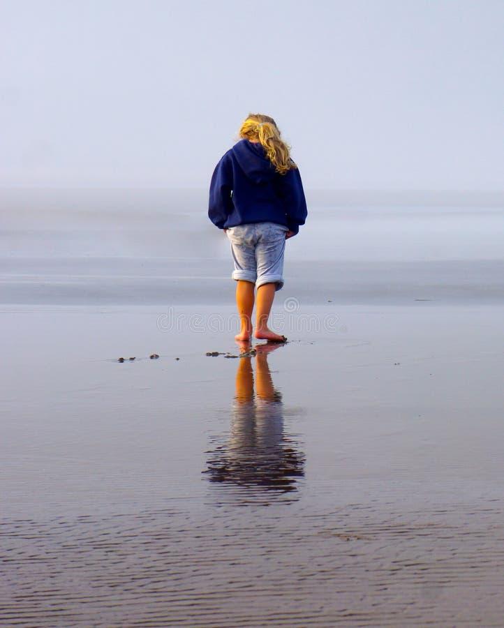 海滩的女孩与在湿沙子的反射 免版税库存照片