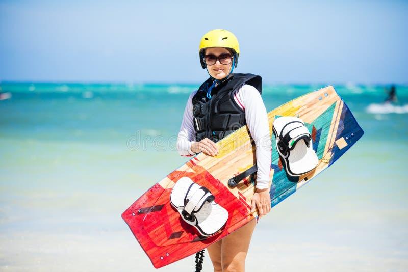 海滩的女孩与她的冲浪板 图库摄影