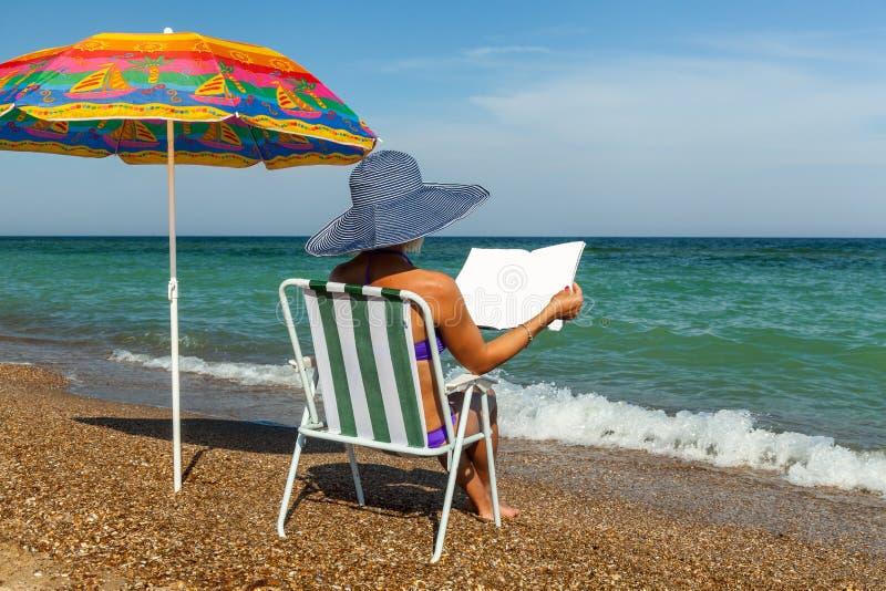 海滩的女孩,晒日光浴,有膝上型计算机的女孩,在a下的妇女 库存照片