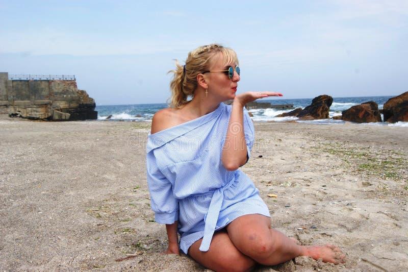 海滩的女孩,由海的金发碧眼的女人 蓝色礼服女孩 免版税库存照片