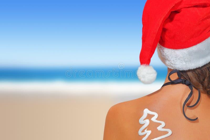 海滩的妇女在圣诞老人帽子 免版税库存图片
