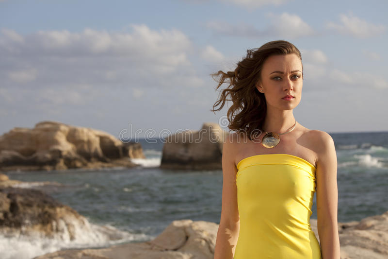 海滩的妇女由日落 免版税库存图片