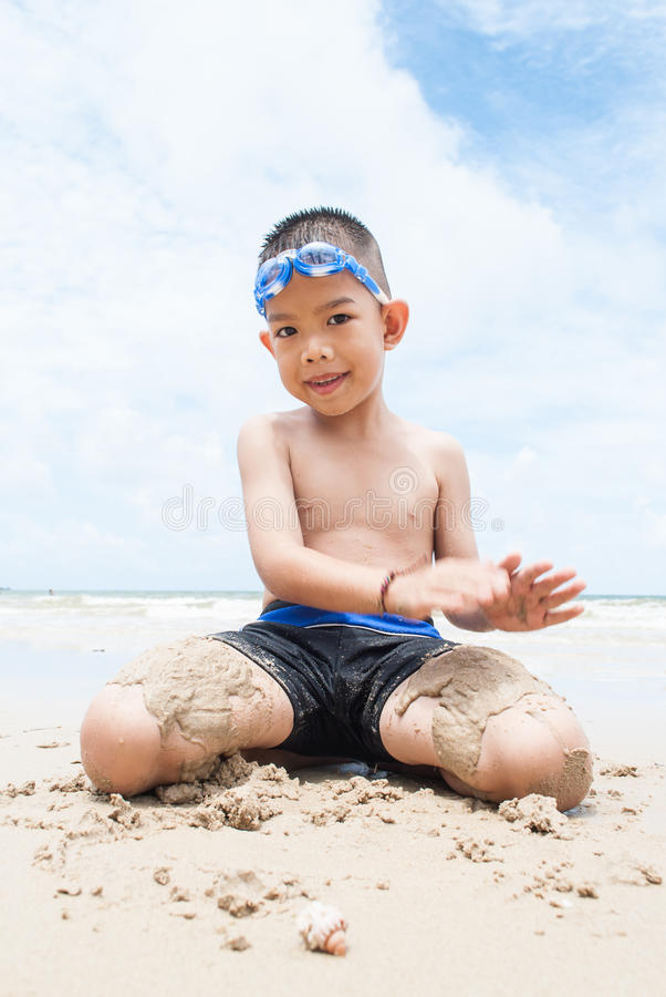 海滩的嬉戏的男孩与背景的海。 库存照片