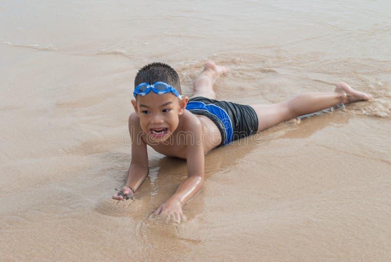 海滩的嬉戏的男孩与背景的海。 免版税库存照片