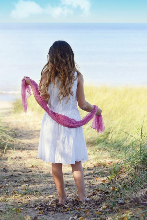 海滩的小女孩与桃红色围巾 免版税图库摄影
