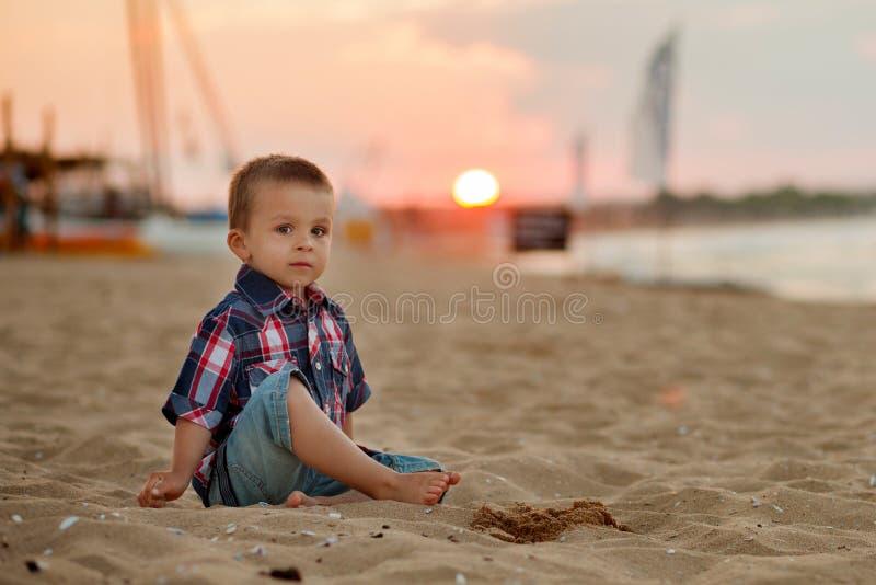 海滩的小男孩,使用与在日落的沙子 免版税库存图片