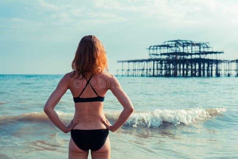 海滩的少妇与遗弃pieer 库存照片