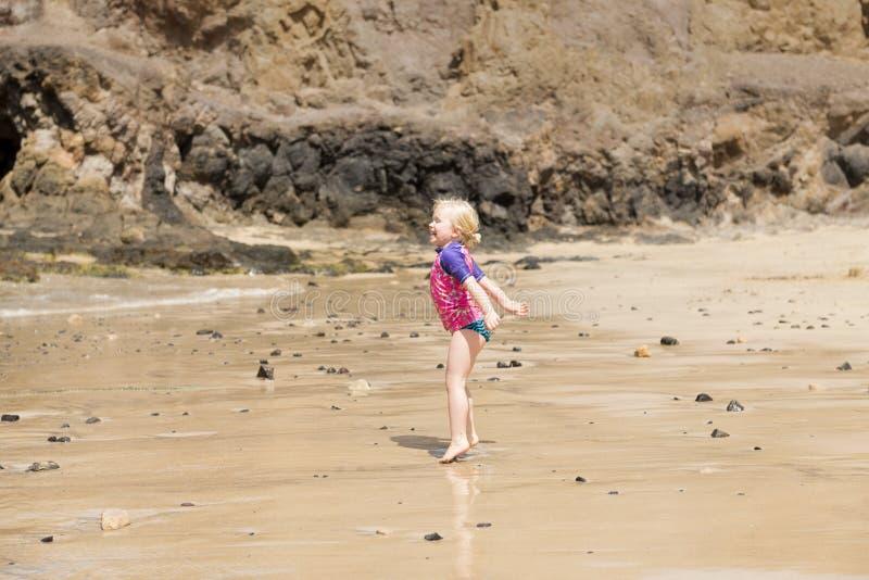 海滩的愉快的跳跃的小女孩 免版税图库摄影