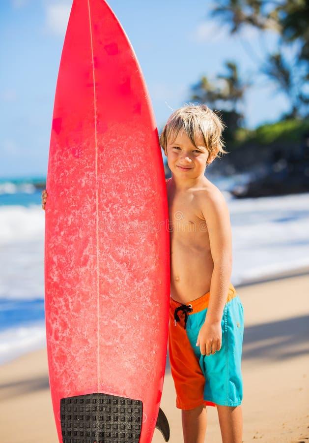 海滩的愉快的年轻男孩与冲浪板 免版税库存照片