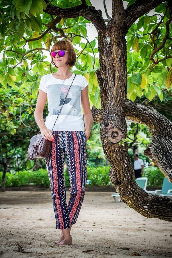 海滩的时尚少妇 豪华snakeskin Python提包在她的手上 晴朗的日 热带海岛巴厘岛 库存图片