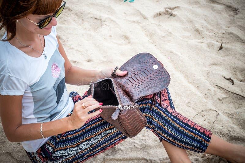 海滩的时尚少妇 豪华snakeskin Python提包在她的手上 晴朗的日 热带海岛巴厘岛 免版税库存照片