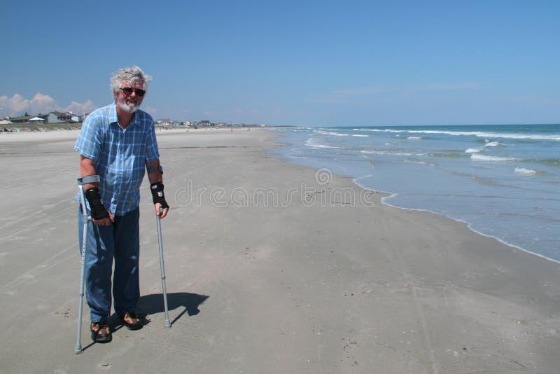 海滩的有残障的资深绅士在夏天 免版税库存照片