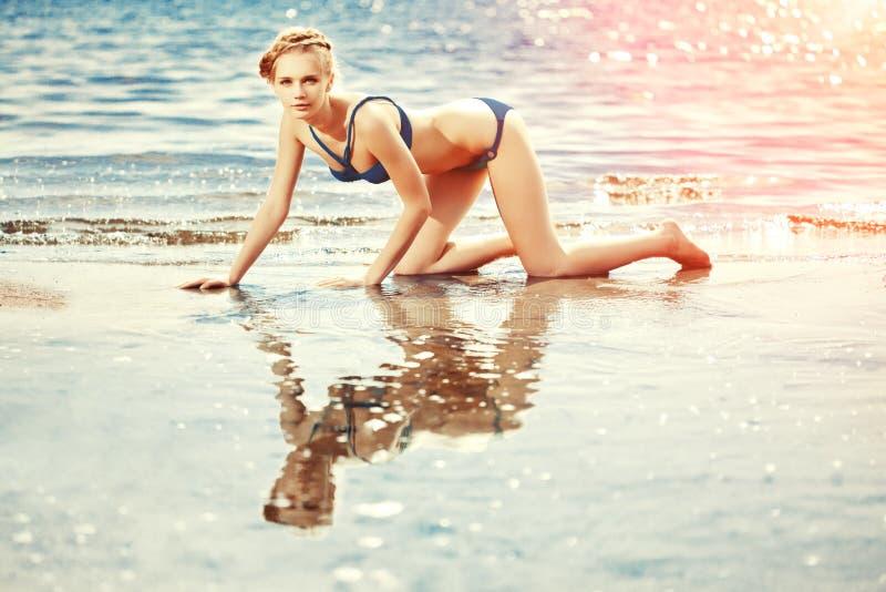 海滩的美丽的妇女由海 库存图片
