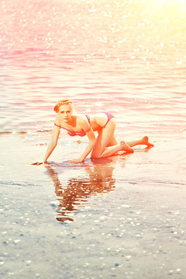 海滩的美丽的妇女由海 库存照片