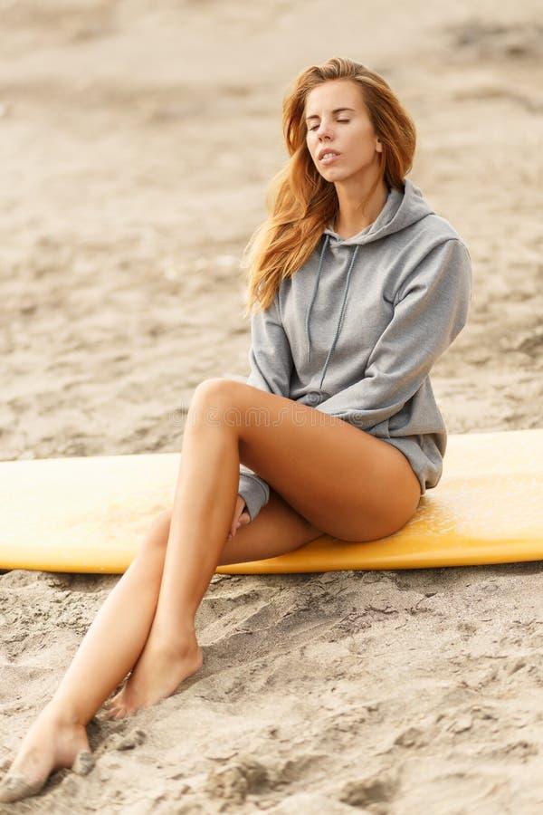 海滩的美丽的运动的冲浪者女孩 库存图片