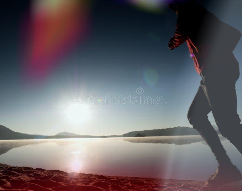 海滩的连续人 运动员在棒球帽跑,跑步人在沙滩上的日出期间 跳在海滩的人在 库存图片