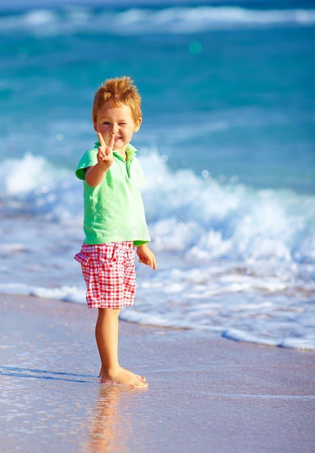 海滩的逗人喜爱的男孩,显示胜利姿态 免版税库存照片