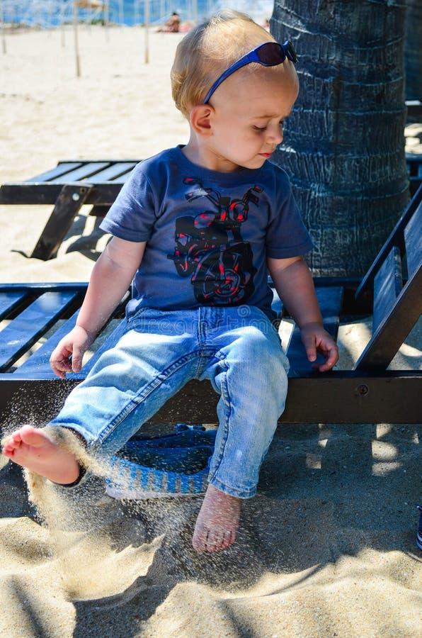 海滩的逗人喜爱的白肤金发的孩子 免版税库存照片
