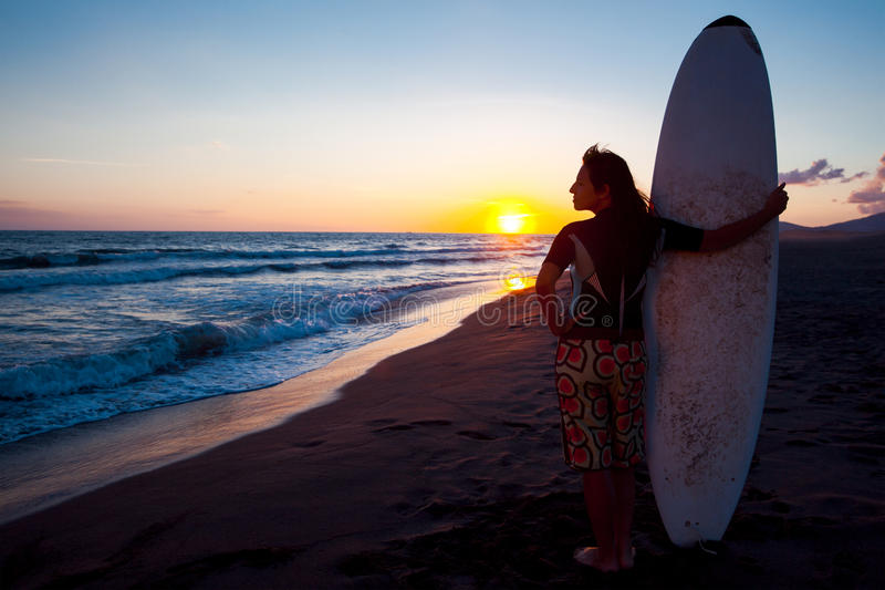 海滩的年轻女性冲浪者在日落 库存照片