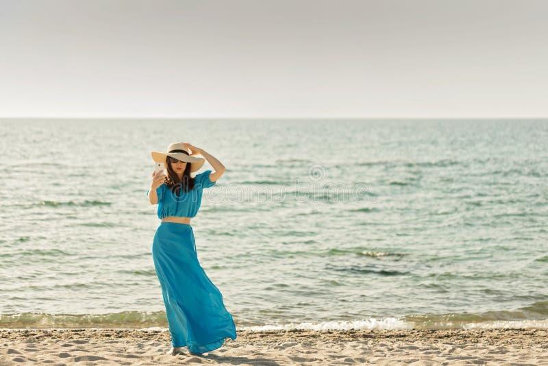 海滩的年轻美丽的妇女在天蓝色的长的礼服采取pic 图库摄影