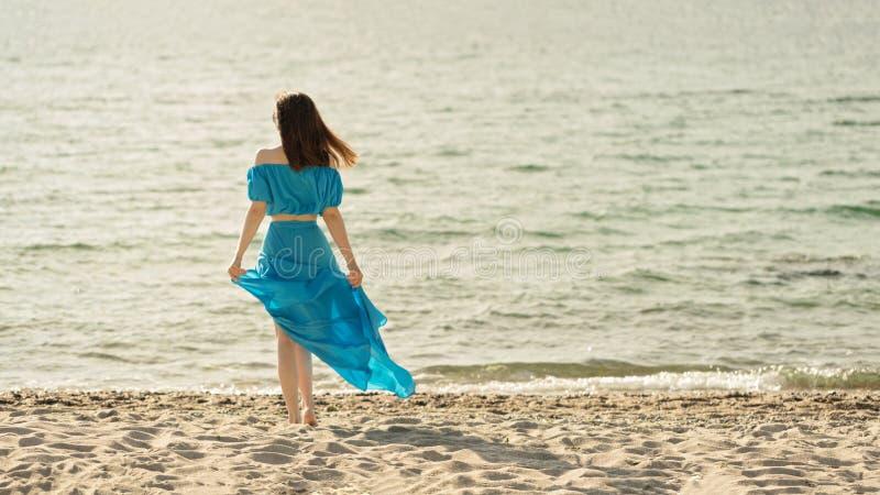 海滩的年轻美丽的妇女在天蓝色的长的礼服 免版税库存照片