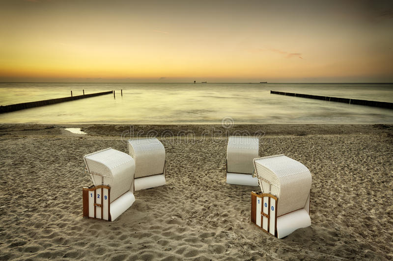 海滩睡椅,日落的波罗的海 免版税库存图片