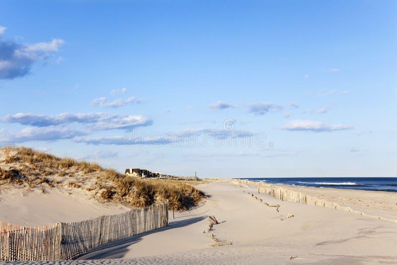 海滩篱芭、沙子、议院和海洋。 免版税库存照片