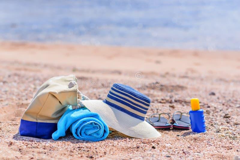 海滩袋子和太阳帽子在晴朗的沙滩 库存照片