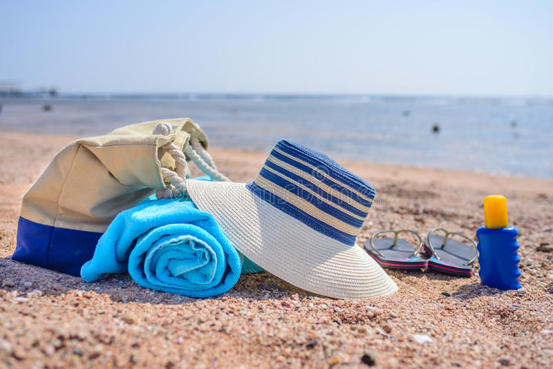 海滩袋子和太阳帽子在晴朗的沙滩 库存图片