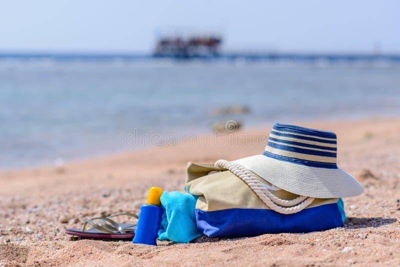 海滩袋子和太阳帽子在晴朗的离开的海滩 库存图片
