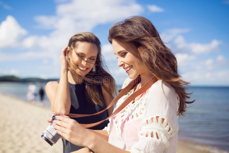 海滩观看的照片的美丽的妇女在与朋友的照相机 免版税库存照片