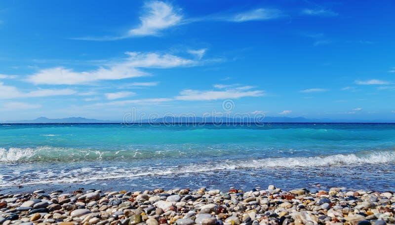 海滩Pebble海滩夏天太阳波浪罗得岛希腊 免版税库存图片