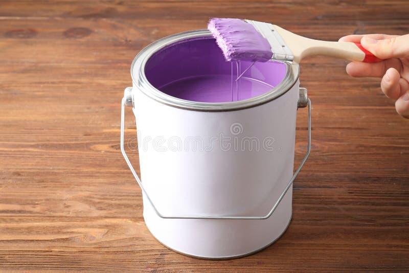 浸洗刷子的妇女入与紫罗兰色油漆的锡罐 图库摄影