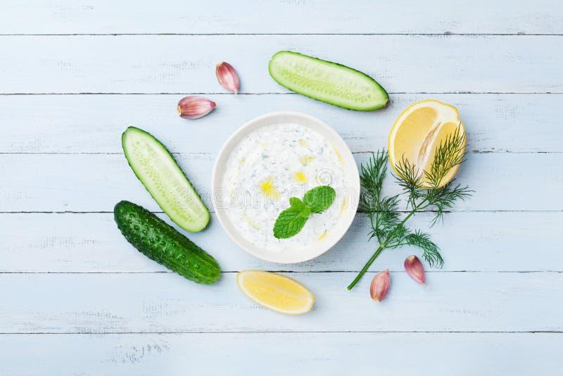 浸洗或穿戴从希腊酸奶的tzatziki与在蓝色木台式视图的成份黄瓜、莳萝、柠檬、薄菏和大蒜 免版税库存照片