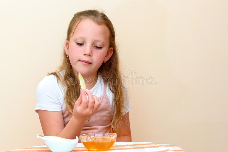 浸洗苹果切片的犹太女孩入在犹太新年的蜂蜜 免版税库存图片