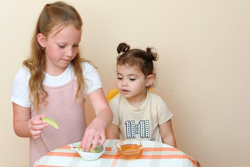 浸洗苹果切片的犹太孩子入在犹太新年的蜂蜜 库存照片