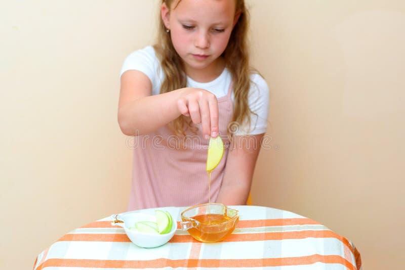 浸洗苹果切片的犹太孩子入在犹太新年的蜂蜜 免版税库存图片