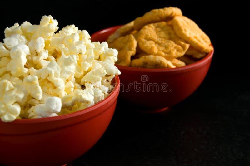 涂奶油的玉米花和BBQ米芯片接近的侧视图在黑色隔绝的红色碗的 库存图片