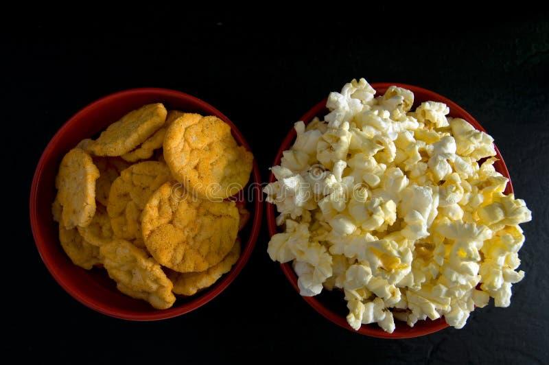涂奶油的玉米花和BBQ米芯片接近的顶视图在黑色隔绝的红色碗的 免版税图库摄影