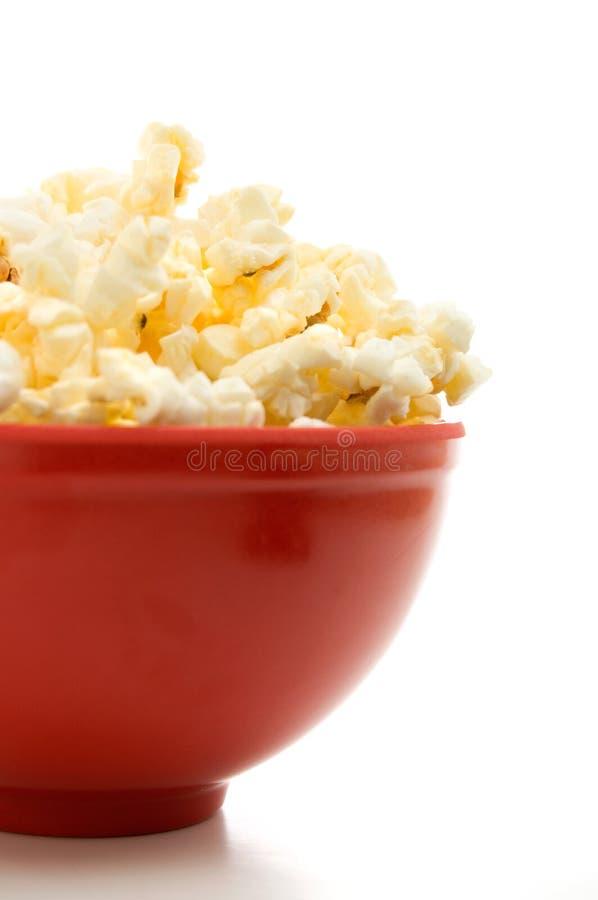 涂奶油的玉米花接近的侧视图在白色隔绝的一个红色碗的 免版税库存图片