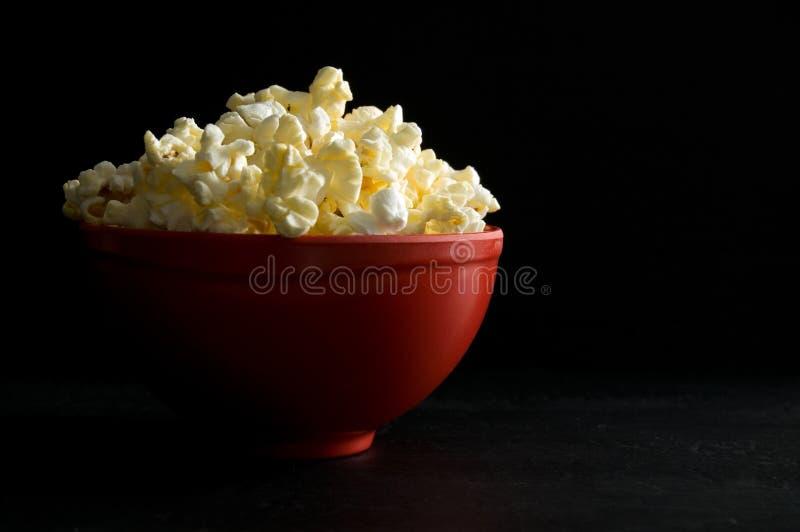 涂奶油的玉米花接近的侧视图在黑色隔绝的一个红色碗的 免版税图库摄影