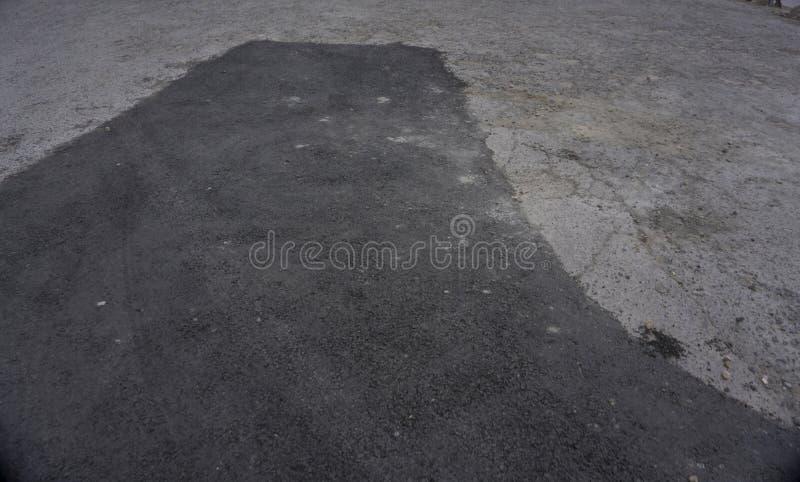 涂柏油在具体地面修理路面路的柏油碎石地面补丁在停车场 免版税库存图片