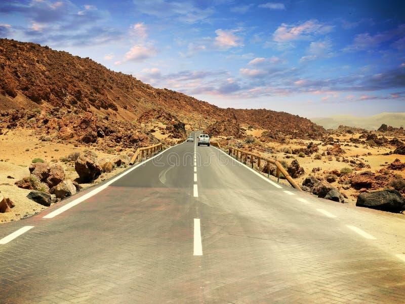 涂柏油在石头之间的高速公路在与云彩的dramatoc天空下 免版税库存照片