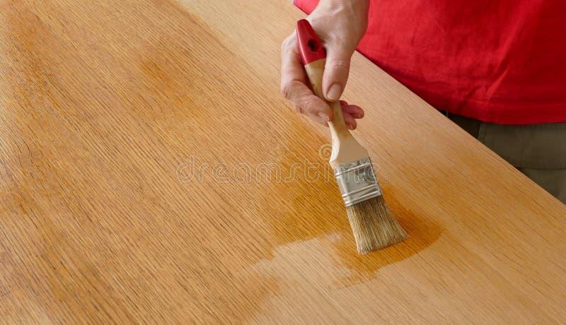 涂清漆木的板条,使用工具的工作者手 免版税图库摄影